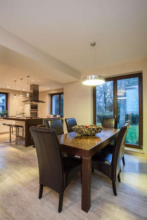 Travertine house - dining room table and a kitchen in a background photo