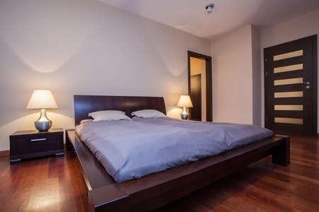 travertine house: Travertino casa - habitaci�n iluminada con una cama de madera Foto de archivo