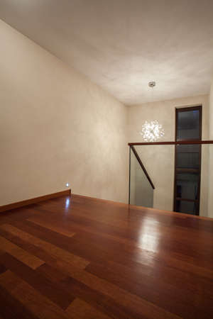Travertine house - vertical view of wooden floor and bright walls photo