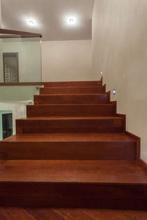Travertine house - Vertical view of brown, wooden stairs in luxury interior photo