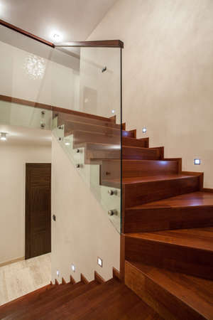 barrier: Travertine house - Wooden glass staircase in modern interior Stock Photo