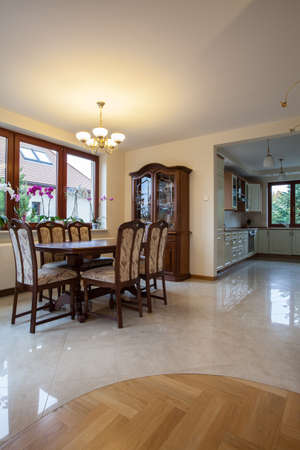 Dining room, kitchen, corridor in traditional beige house photo