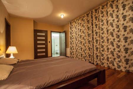 travertine house: Casa Travertino - dormitorio con cama de madera Foto de archivo
