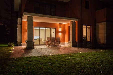 travertine house: Travertino casa - patio con jard�n iluminado