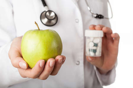 Doctor giving an apple instead of a drugs Stock Photo