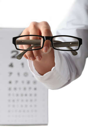 myopia: Doctor s hand giving glasses on eye chart background