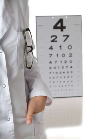 astigmatism: Optometrist in white apron and eye chart Stock Photo