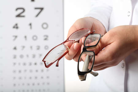 Optometrist holding two pair of glasses, eye chart photo