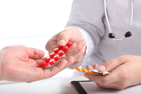 doctor giving pills: Closeup of physician s hands giving blisters of pills