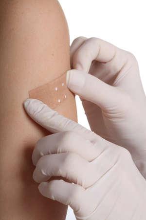 herida: Enfermera en guantes poner una tirita sobre la herida
