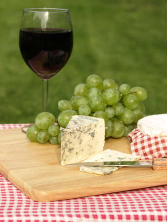 Closeup of blue cheese with full glass and grapes photo