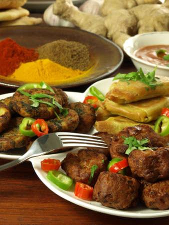 Closeup of samosas, bhajis and sag aloo frittes photo