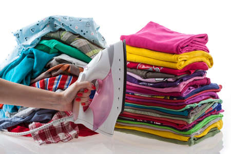 Hand holding iron with colorful laundry Stock Photo - 17061565