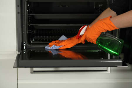 cleaning kitchen: Hand in gloves with rubber cleaning an oven Stock Photo