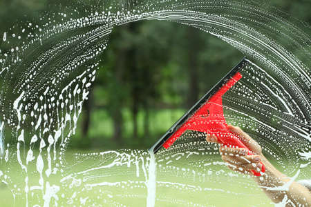 garden staff: Windows claening, glass without smudges red squeegee Stock Photo
