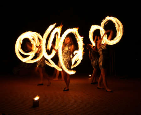 fire show: Woman dancers with a fire, night show Stock Photo