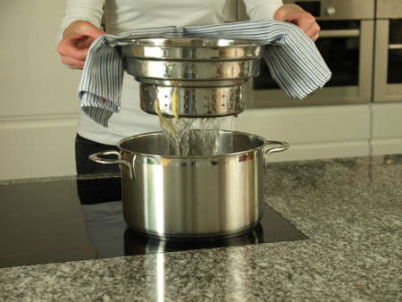 Woman draining spaghetti with colander photo