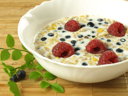 Bowl of milk with fruits and oat flakes photo
