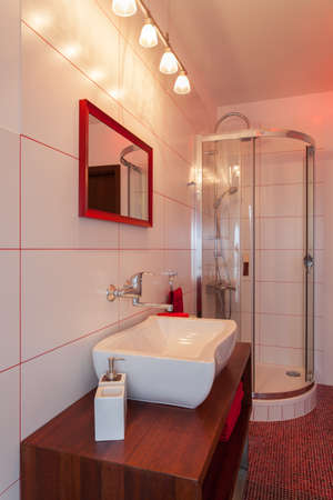 Ruby house - Wash basin and shower in red and white bathroom photo
