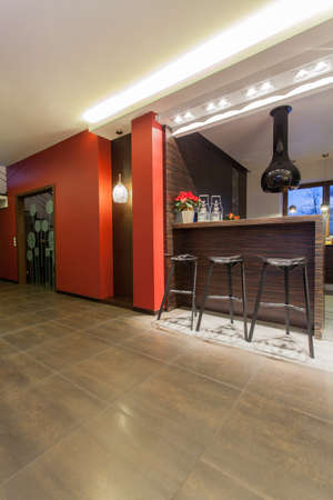 bar top: Ruby house - Red and modern kitchen with bar stools Stock Photo