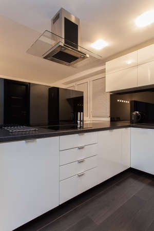 Minimalist apartment - black kitchen counter and white furniture photo