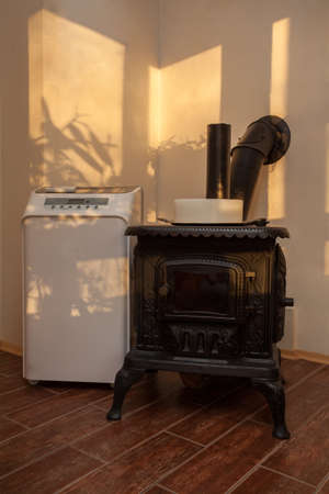Cloudy home - old cast-iron stove in a living room photo