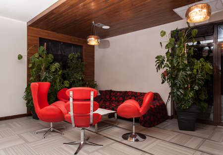 woodland hotel: Woodland hotel - Modern interior with a red sofa and armchairs Stock Photo