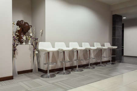 Woodland hotel - Six white bar stools in modern interior photo