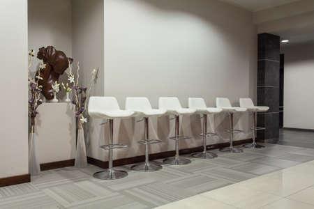 Woodland hotel - Six white bar stools in modern interior Stock Photo - 17502416