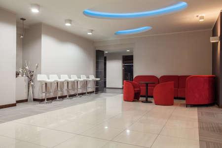 furnish: Woodland hotel - Waiting room with stools and sofa
