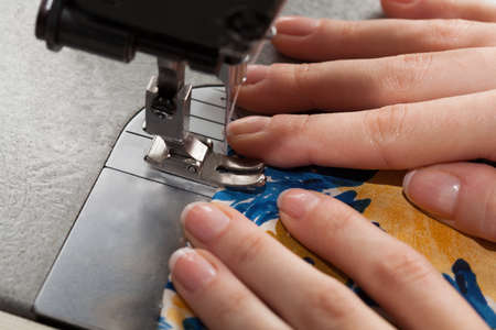 stitching machine: Closeup of dressmakers hands and a dress Stock Photo