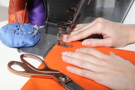 stitching machine: Dressmaker using an orange fabric to make a dress Stock Photo