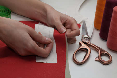 out of production: Dressmaker cutting piece of material for a clothing Stock Photo