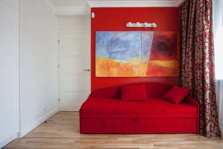 Teenagers room with a red wall and sofa photo