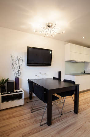 Stylish flat - Diming room with a black table and TV Stock Photo - 17749208