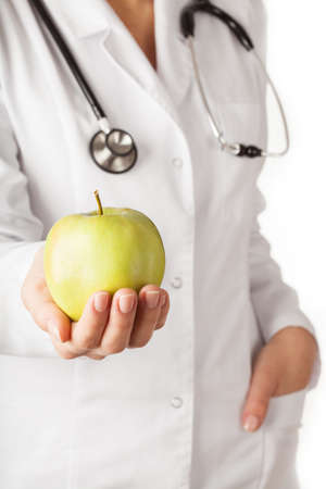 health care decisions: Doctor holding a big green apple, concept shot