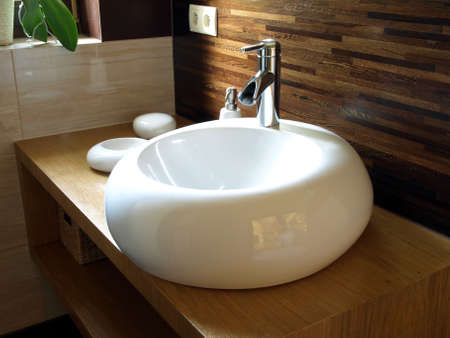 Closeup of round white sink in modern bathroom