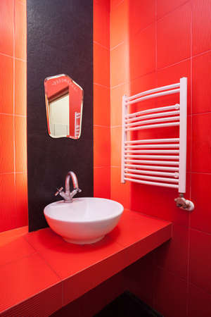 Interior of red bathroom with wash basin and heater photo