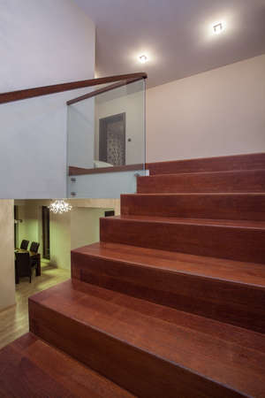 stair well: Travertine house- Brown wooden stairs in luxury interior