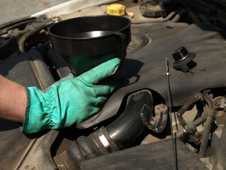Man hand pouring oil in car engine photo