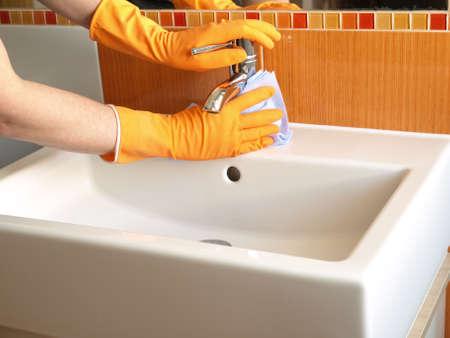 servicio domestico: Las manos en guantes con grifer�a de la ba�era de caucho de limpieza Foto de archivo