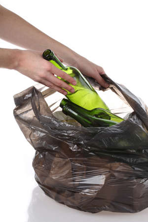 discarded metal: Mans hands putting glass bottles into plastic bag Stock Photo