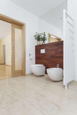 bidet: Toilet and bidet in bathroom with exotic wood
