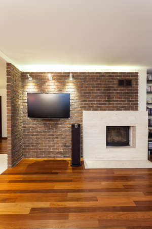 Spacious apartment - brick wall with fireplace and tv Stock Photo - 18522883