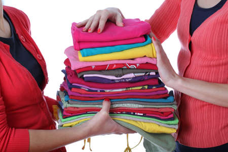 fold: Women holding pile of ironed and colorful clothes Stock Photo