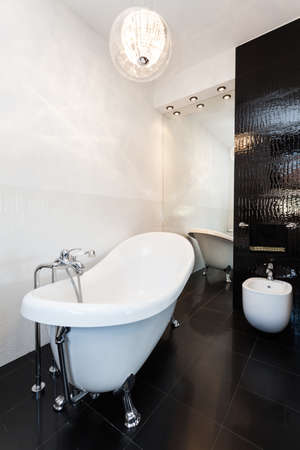 vibrant cottage: Vibrant cottage - Black and white bathroom with classic bathtub