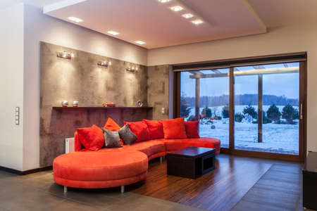 living room design: Ruby house - Huge, red and comfortable sofa Stock Photo