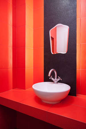 Red bathroom, wash basin and mirror photo