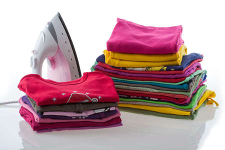 Arranged, colorful laundry and iron on isolated beckground photo