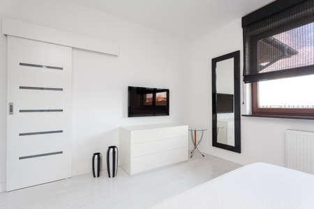 Яркие коттедж - белый и черный комод телевизор в спальне